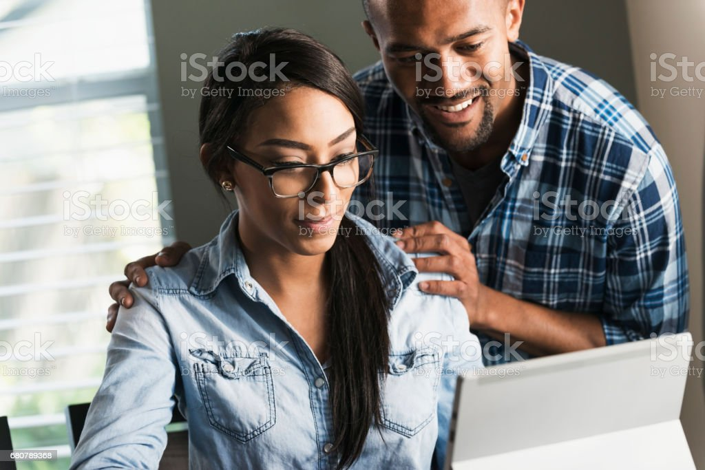Young black couple, woman on computer stock photo