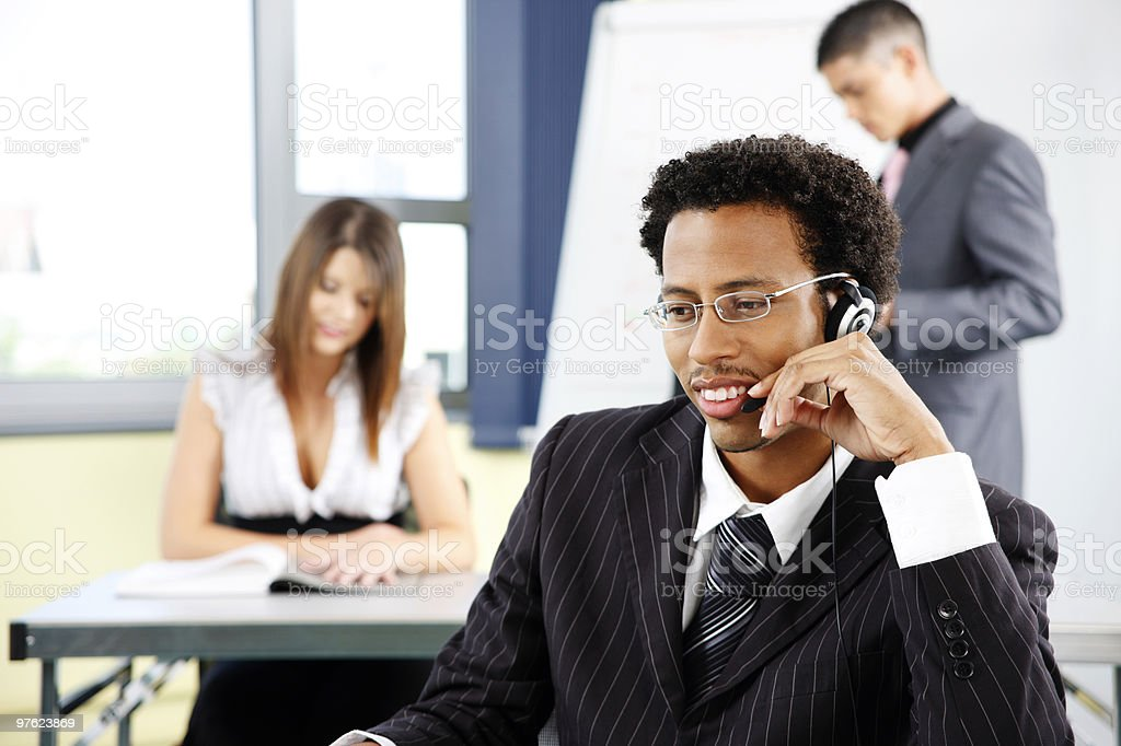young black customer service representative working with colleagues in office royalty-free stock photo