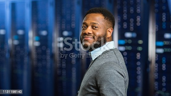 1131208605 istock photo Young Black Data Center IT Technician Standing in Server Rack Corridor and Smiling to the Camera. 1131198140