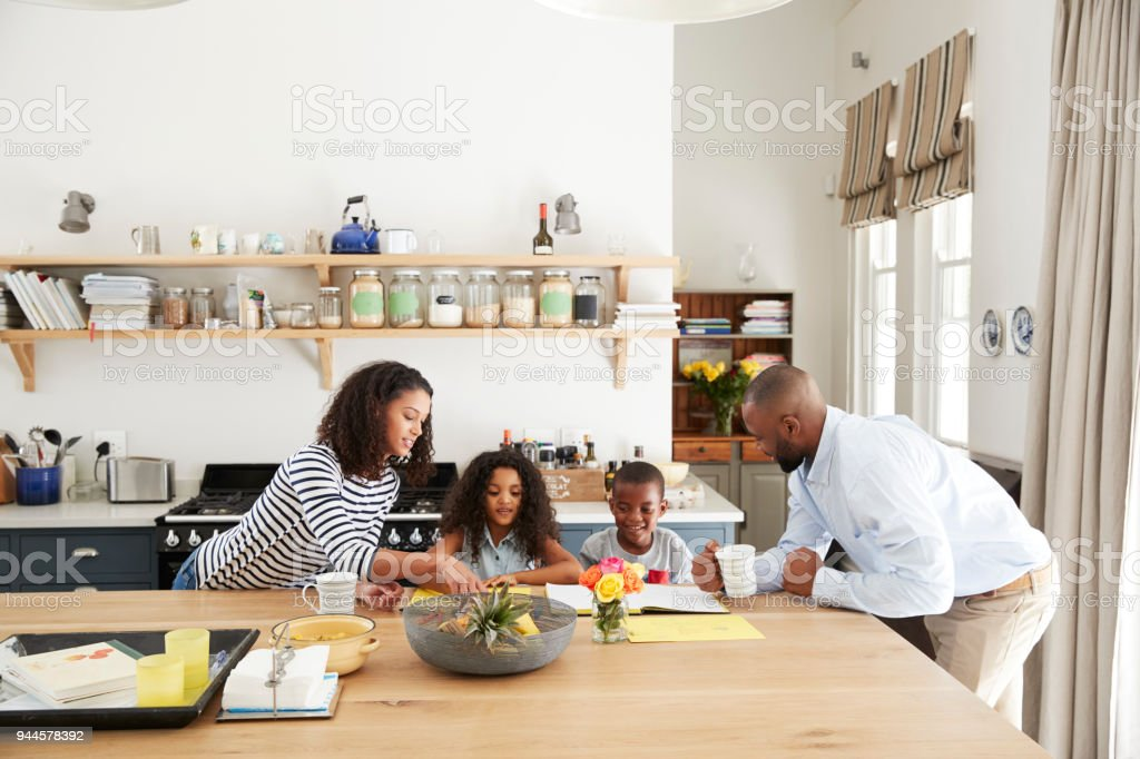 Young black family busy together in their kitchen stock photo