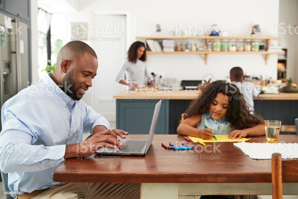 Young black family busy working in their kitchen stock photo