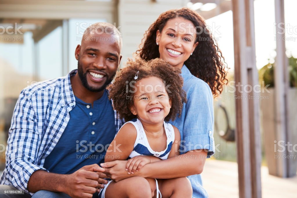 Young black family embracing outdoors and smiling at camera stock photo