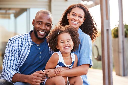 Photo libre de droit de Jeune Noire Famille Embrassant À Lextérieur Et Souriant À La Caméra banque d'images et plus d'images libres de droit de Adulte