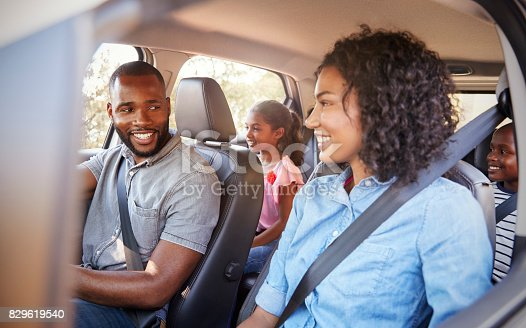 istock Young black family in a car on a road trip smiling 829619540