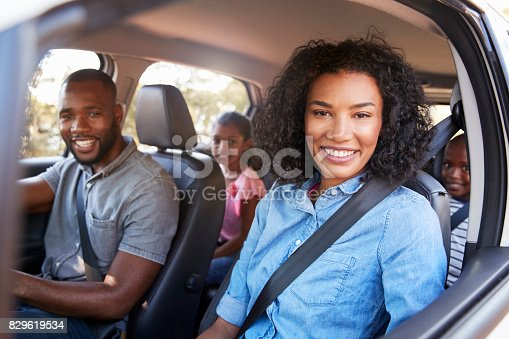 829619540 istock photo Young black family in a car on a road trip smiling to camera 829619534