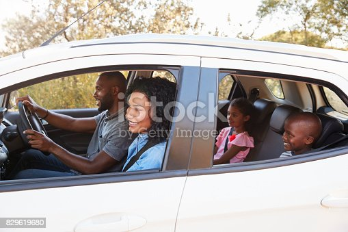 istock Young black family in a car smile on the road trip 829619680