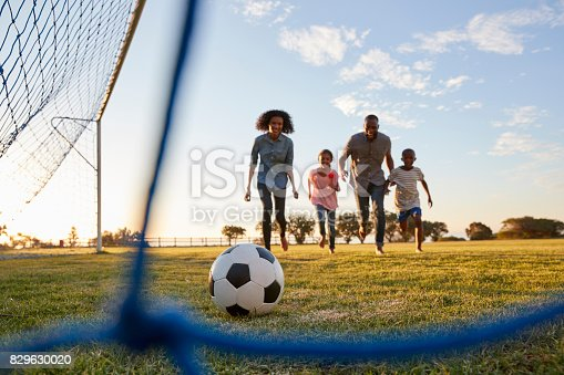829627936istockphoto A young black family running after a football during a game 829630020