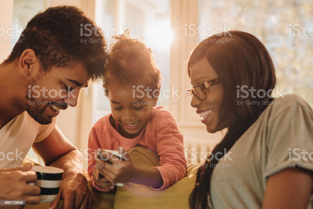 Young black family watching something on mobile phone at home. - Royalty-free Adult Stock Photo