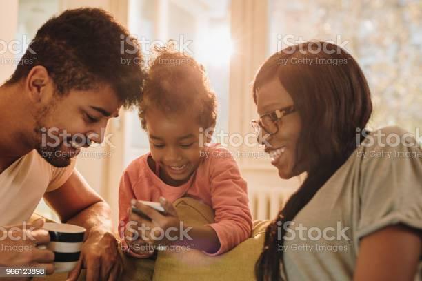 Ung Svart Familj Titta På Något På Mobiltelefonen Hemma-foton och fler bilder på Afrikanskt ursprung