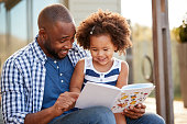 Young black father and daughter reading book outside