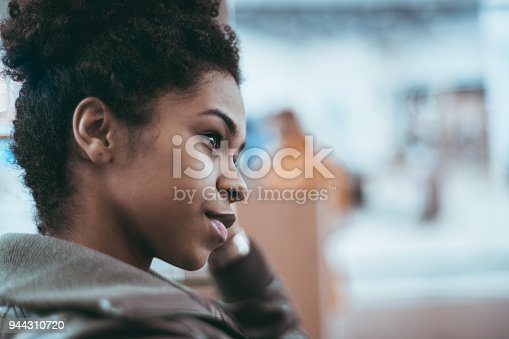 istock Young black female is looking aside, portrait 944310720