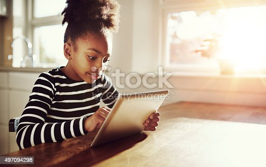 istock Young black girl browsing on a tablet-pc 497094298