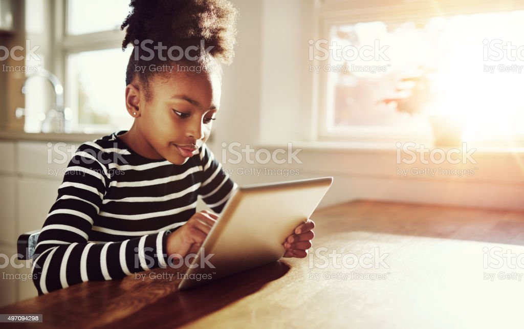 Young black girl browsing on a tablet-pc stock photo