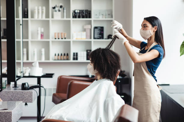 Young black girl in protective face mask getting haircut at hairdressers stock photo