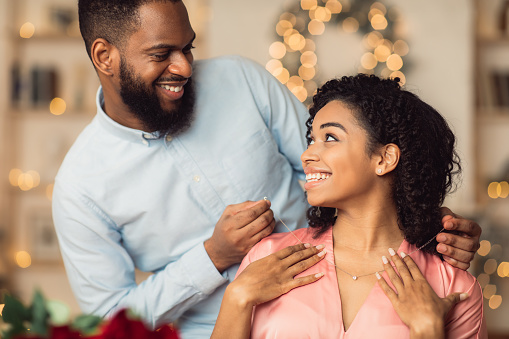 Luxury Present. Smiling Black Young Lady Receiving Golden Pendant Necklace With Diamond For Holiday. Happy Lovely Couple Celebrating St Valentine's Day, Anniversary, Engagement Or Birthday
