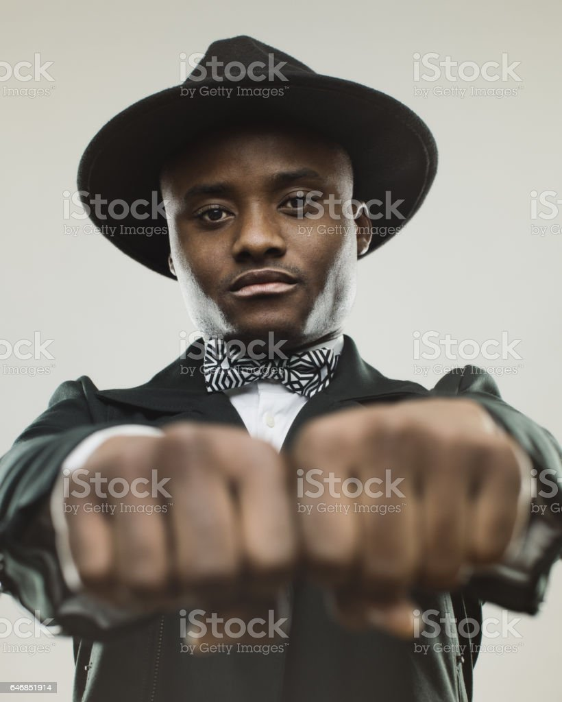 Young black male model in retro suit with fist up stock photo