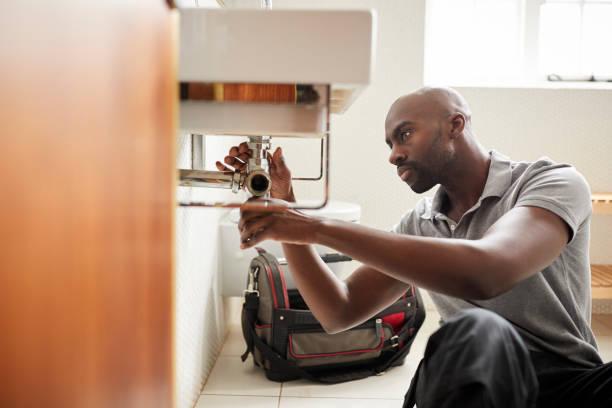 joven fontanero macho negro sentado en el suelo de un lavabo del baño, visto desde la puerta de fijación - fontanero fotografías e imágenes de stock