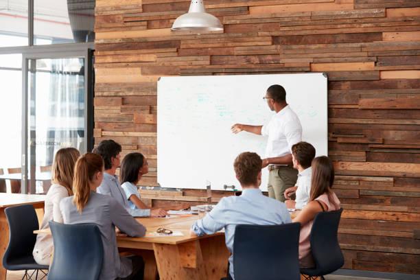 Jovem negro no whiteboard dando uma apresentação de negócios - foto de acervo