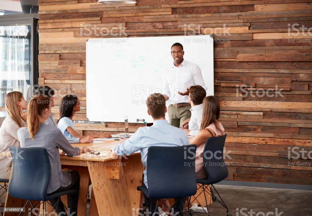 Young black man at whiteboard giving a business presentation stock photo