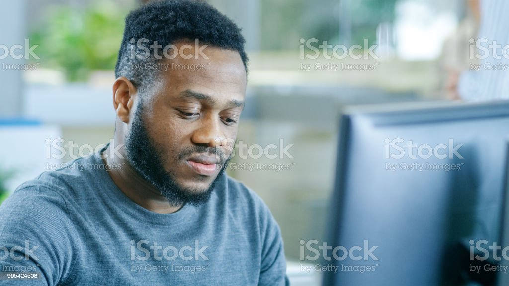 Young Black Man Diligently Works on a Personal Computer in the Corporate Office. Stylish Smart Man with a Trimmed Beard. royalty-free stock photo