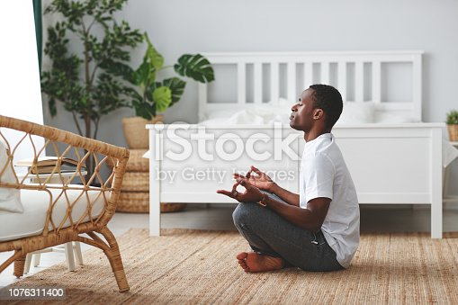 istock young black man doing yoga and sitting in lotus position at home in bedroom 1076311400