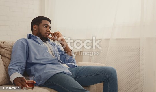 istock Young black man drinking alcohol at home feeling lonely 1130479299