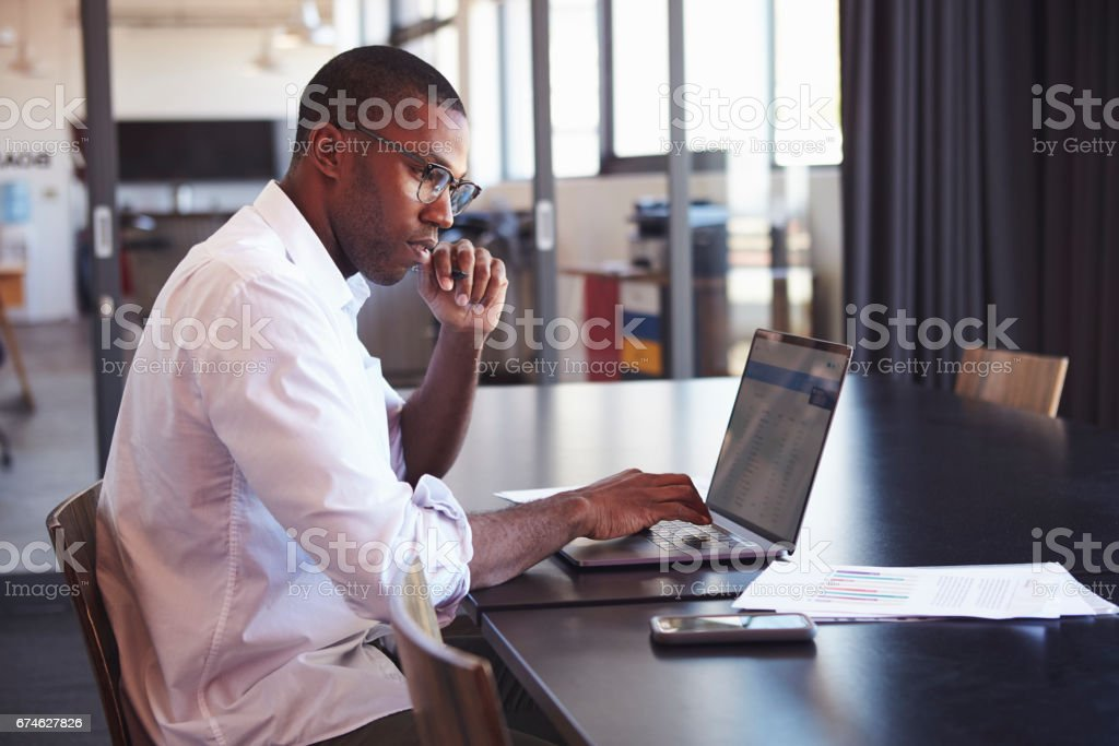 Young black man in wearing glasses using laptop in office Young black man in wearing glasses using laptop in office Research Stock Photo