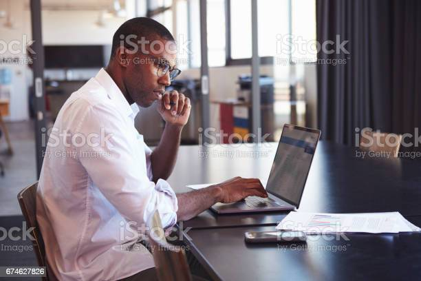 Young Black Man In Wearing Glasses Using Laptop In Office Stock Photo - Download Image Now
