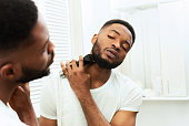 istock Young black man looking at mirror and shaving beard with trimmer 1182647972