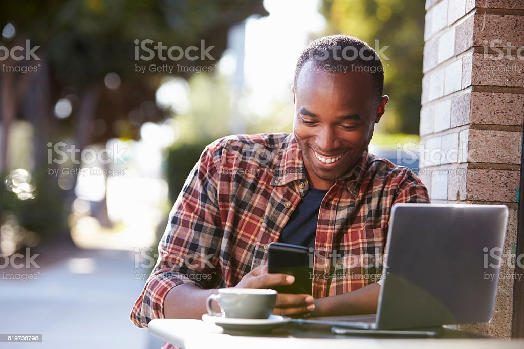 Young black man outside a cafe looking at his smartphone stock photo