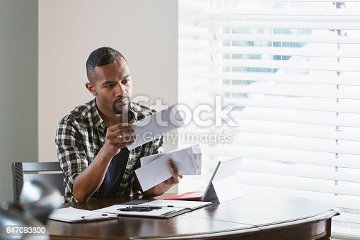 istock Young black man paying bills at home 647093800