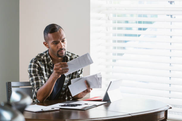 Young black man paying bills at home stock photo