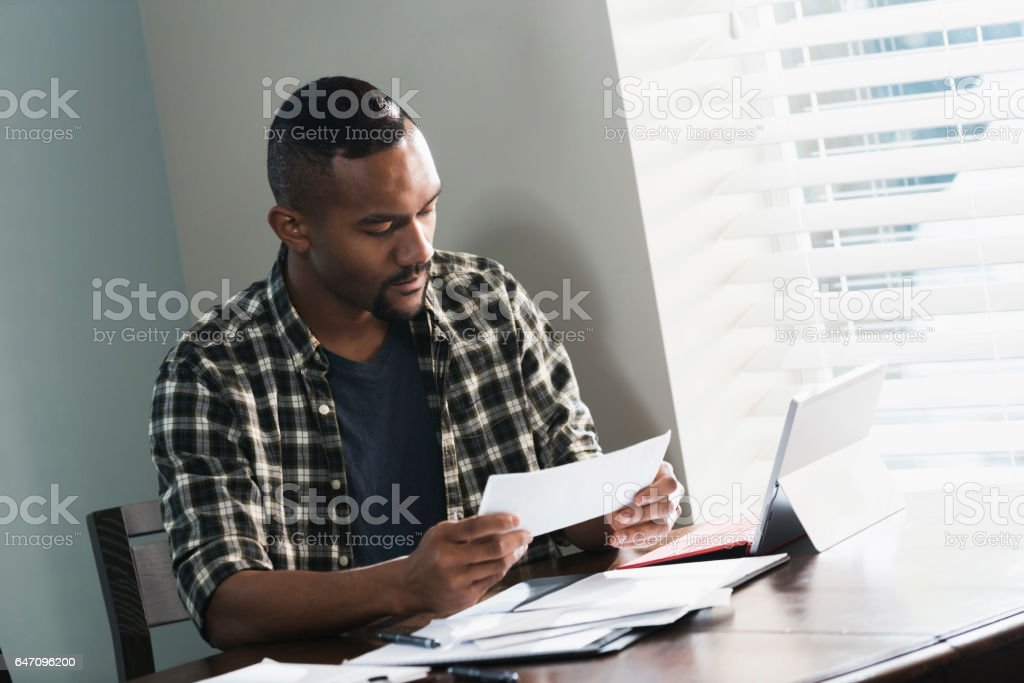 Young black man paying bills at home stock photo