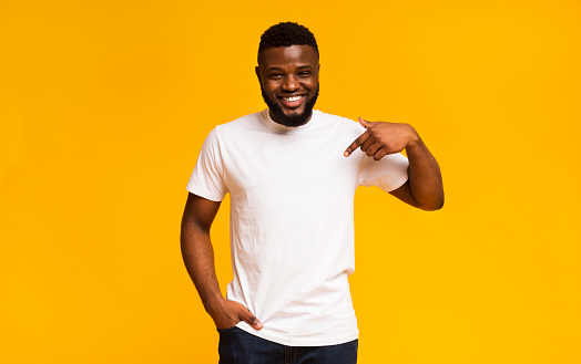 Young black man pointing at blank space of his clothes
