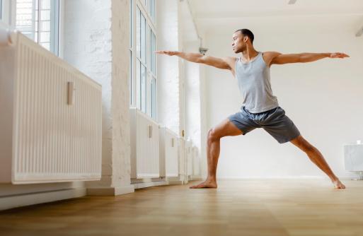 Young black man practicing the Warrior yoga pose. Horizontal shot.