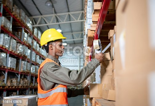 Young black man preparing a delivery taping packages at a warehouse - Business industry concepts