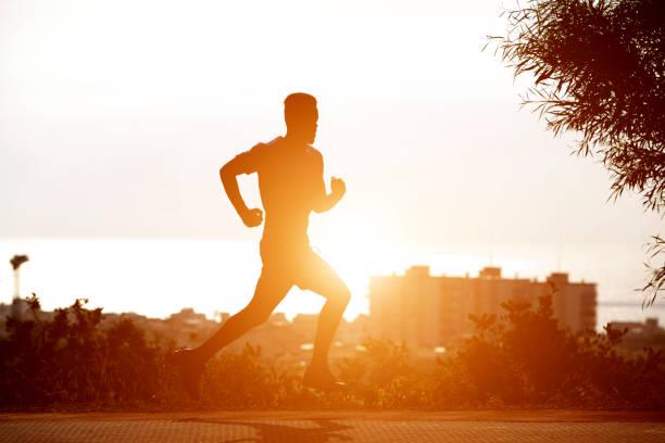 Junge schwarze Mann läuft im Sonnenuntergang – Foto