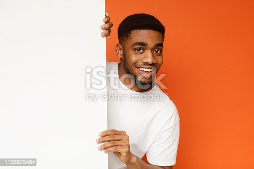 istock Young black man showing and displaying empty placard 1133825484