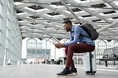 Side portrait of young black man sitting on suitcase at station with mobile phone