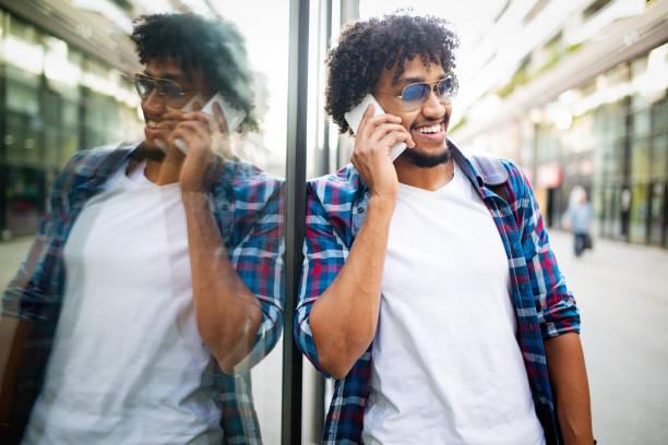 Junger schwarzer Mann lächelt und redet auf Handy draußen – Foto
