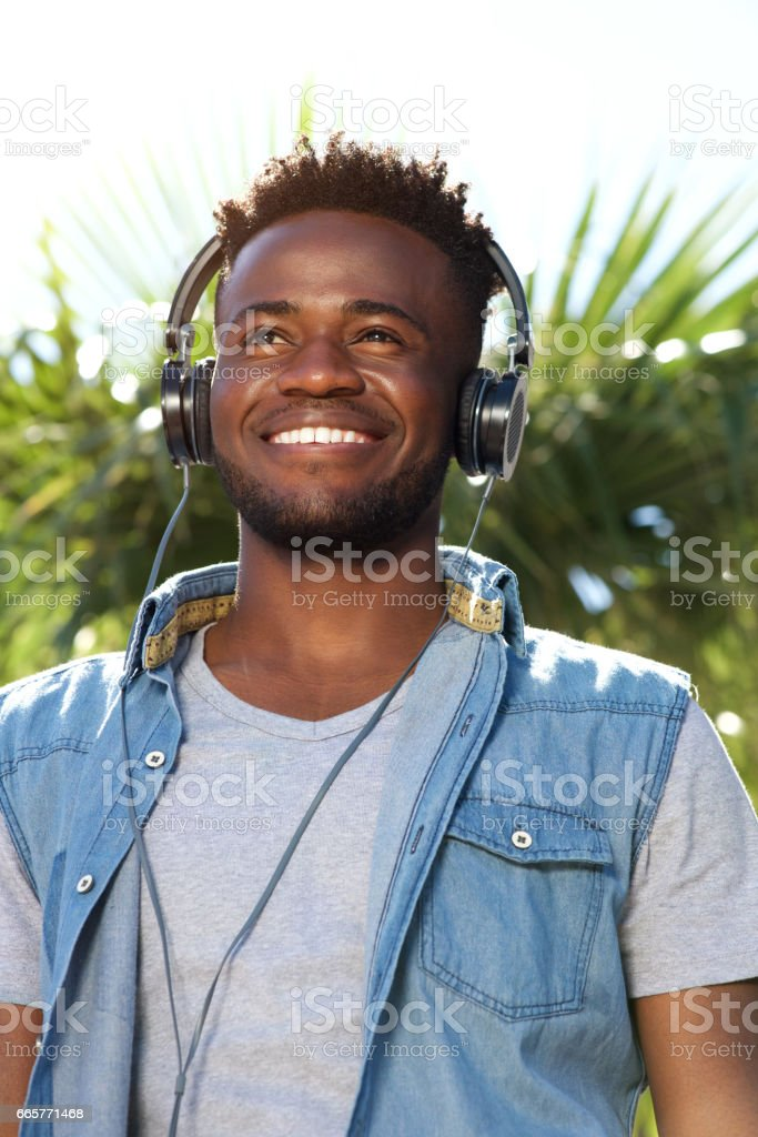young black man smiling with headphones outside stock photo