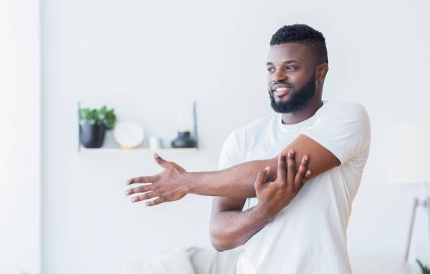 Junger schwarzer Mann trainiert und dehnt Arm zu Hause – Foto