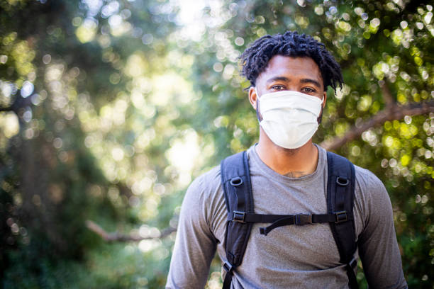 Young Black Man Wearing a Face Mask while Hiking stock photo