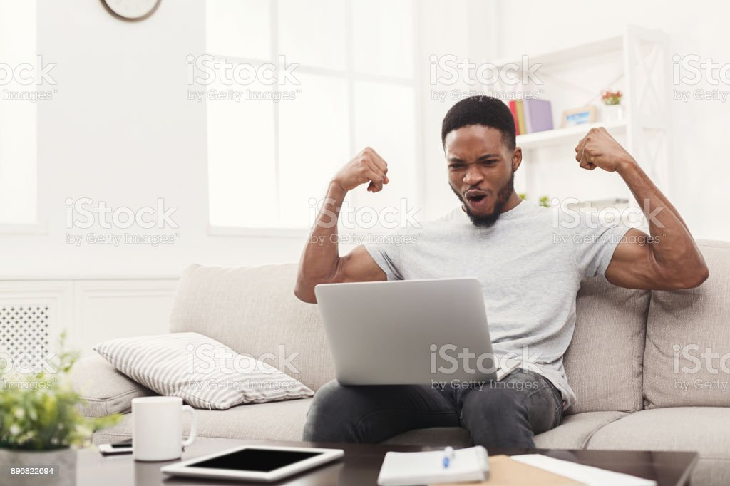 Young black man with arms raised with laptop celebrating success stock photo