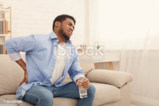 Young african-american man with back pain, pressing on hip with painful expression, sitting on sofa at home with glass of water, copy space