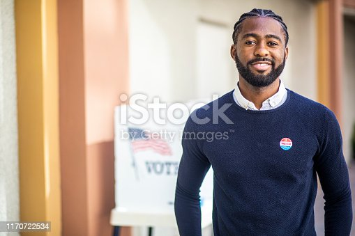 A young black man with his I voted sticker after voting in an election.