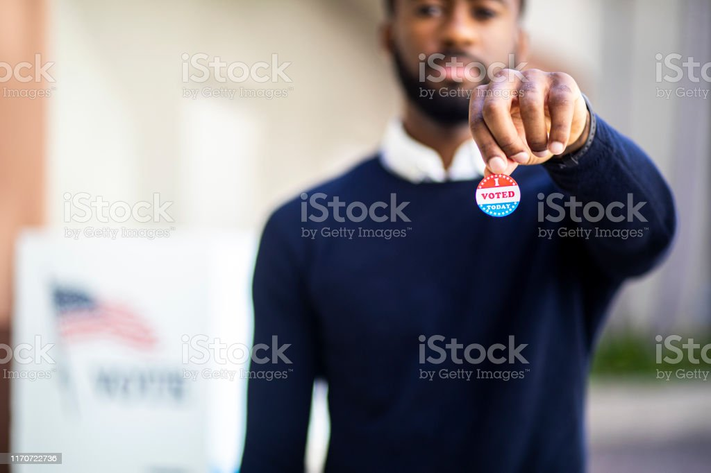 Young Black Man with I voted Sticker A young black man with his I voted sticker after voting in an election. 2020 Stock Photo