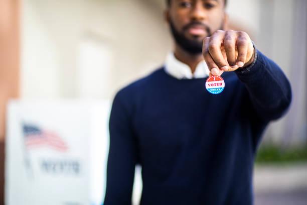 joven negro con yo votado pegatina - voting fotografías e imágenes de stock