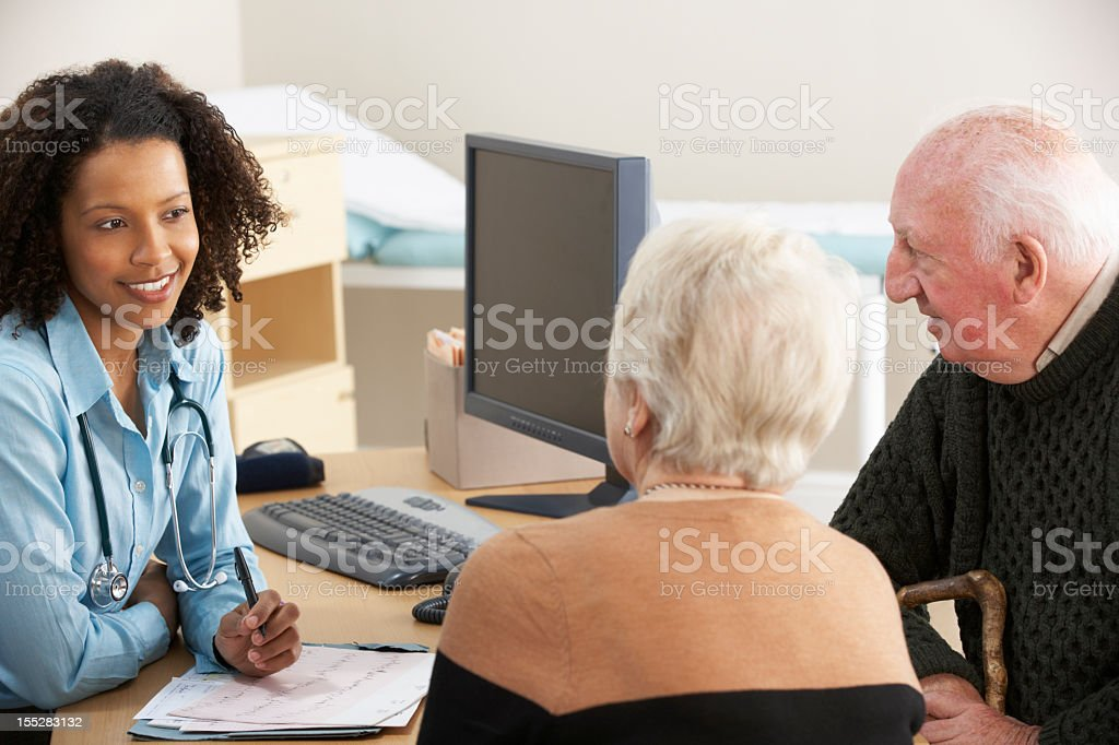 A young, black nurse talking to an elderly couple royalty-free stock photo