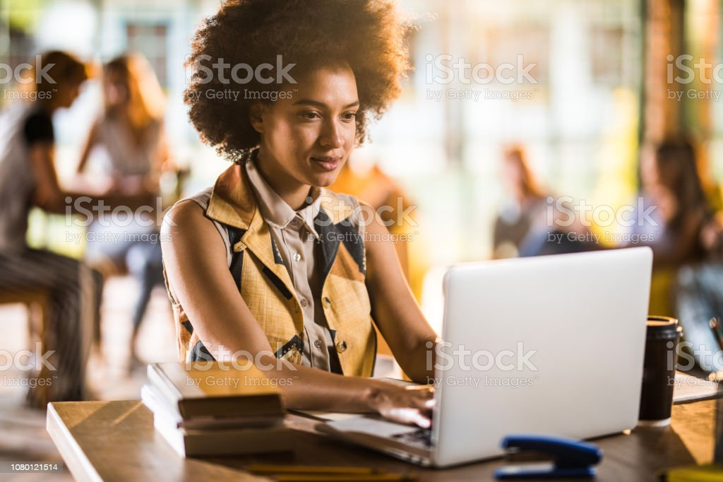 Smiling African American student studying while using laptop in...
